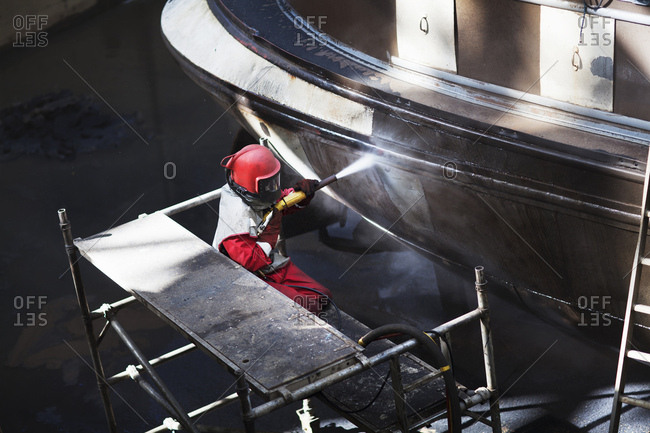 Worker cleaning hull of boat with high pressure hose in shipyard
