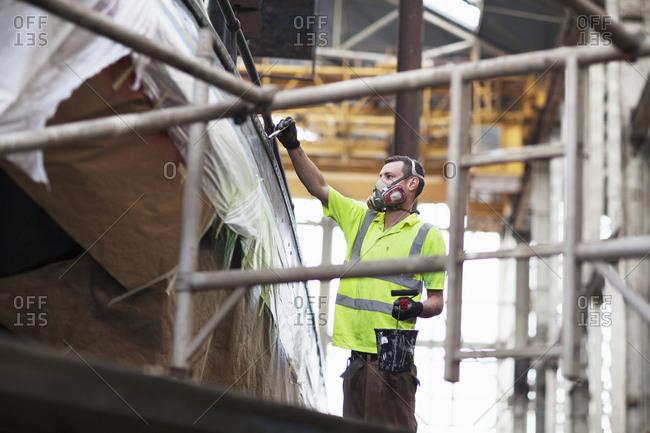 Worker on scaffold painting boat in shipyard workshop