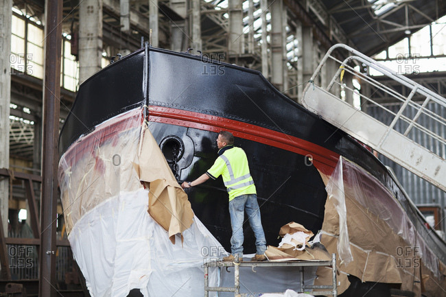 Workers unwrapping boat in shipyard