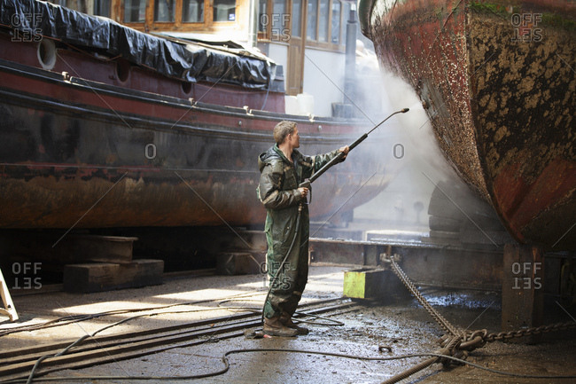 Worker cleaning boat with high pressure hose in shipyard