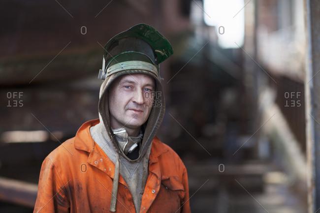 Portrait of welder wearing welding mask in shipyard workshop