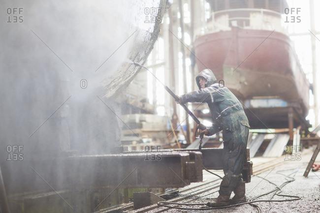 Worker using high pressure hose on boat in shipyard workshop