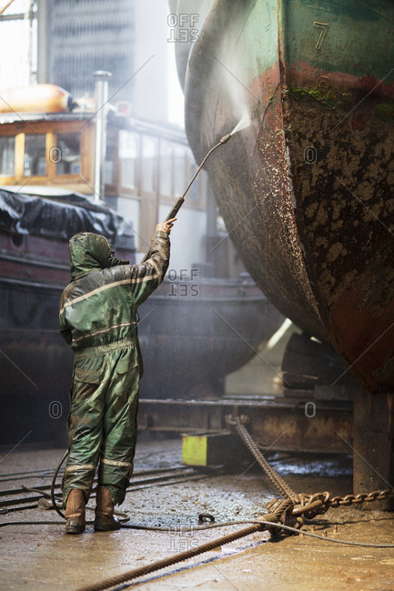 Rear view of worker cleaning boat with high pressure hose in shipyard