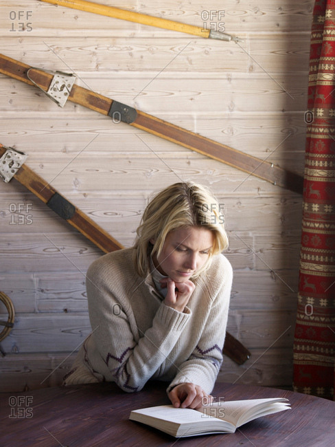 woman reading in ski lodge table