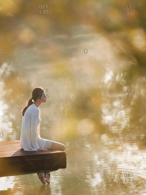 Woman dangling her feet in lake