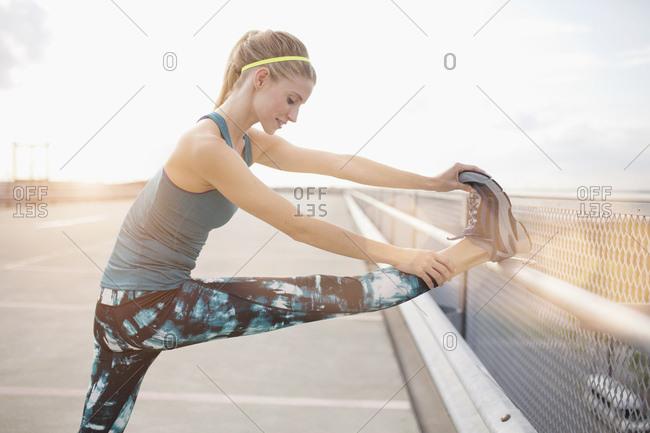 Young woman stretching leg