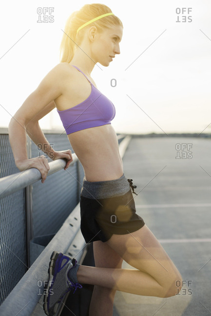 Young woman wearing sports clothes leaning against fence