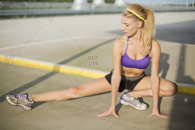 Young woman crouching and stretching leg