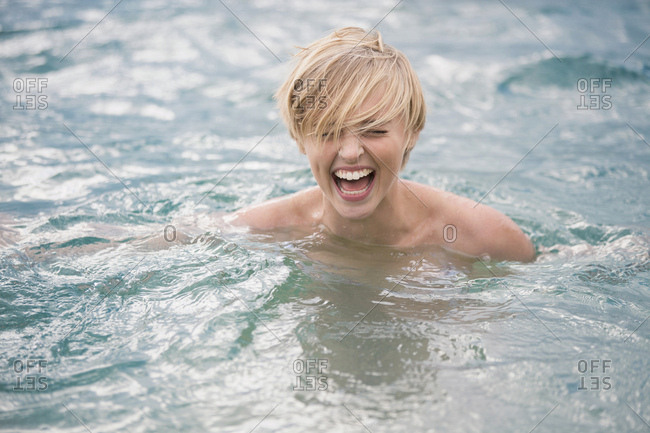 Happy bare shouldered young woman in lake