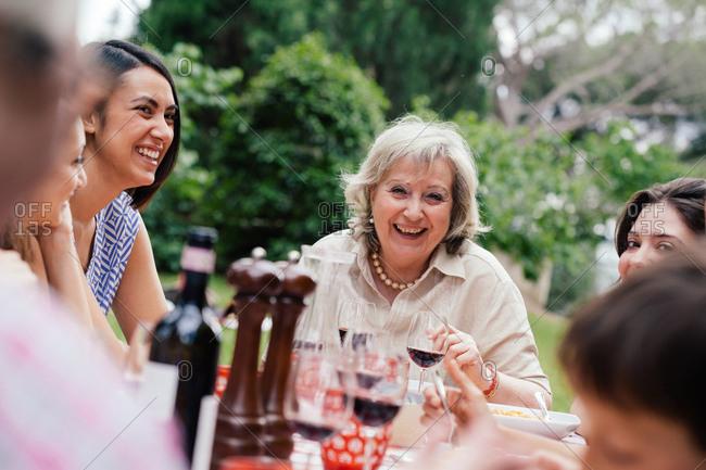 Senior woman enjoying meal with family
