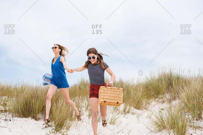 Two young female friends carrying picnic basket running on sand dunes