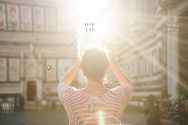 Rear view of mid adult woman, arms raised, lens flare, Duomo Cathedral, Florence, Italy