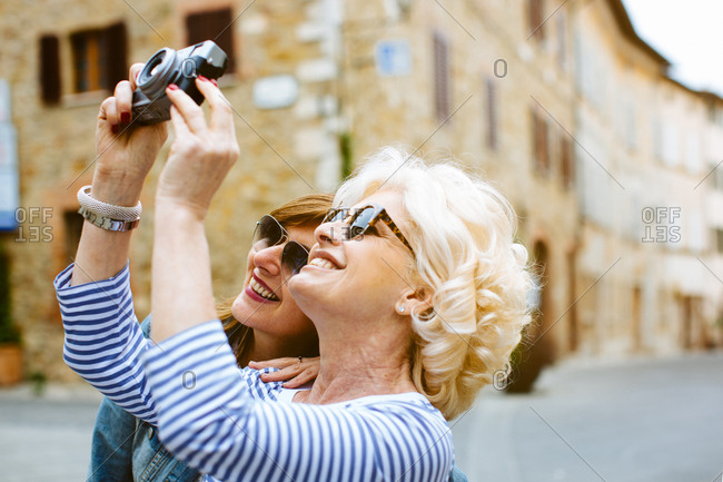 Two mature female friends photographing, Tuscany, Italy