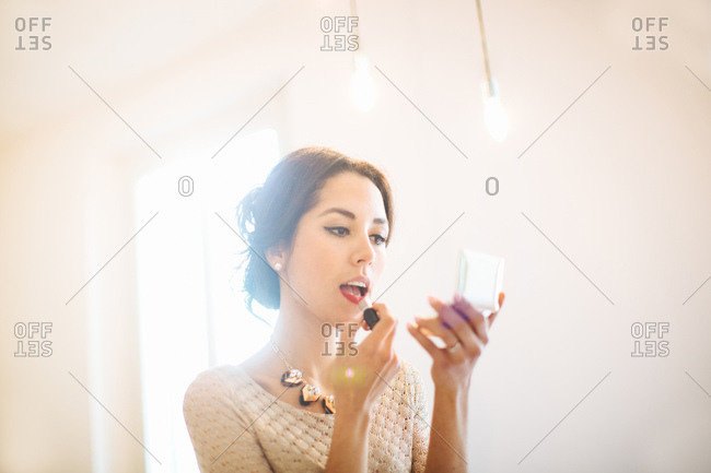 Stylish young woman applying lipstick at home before night out