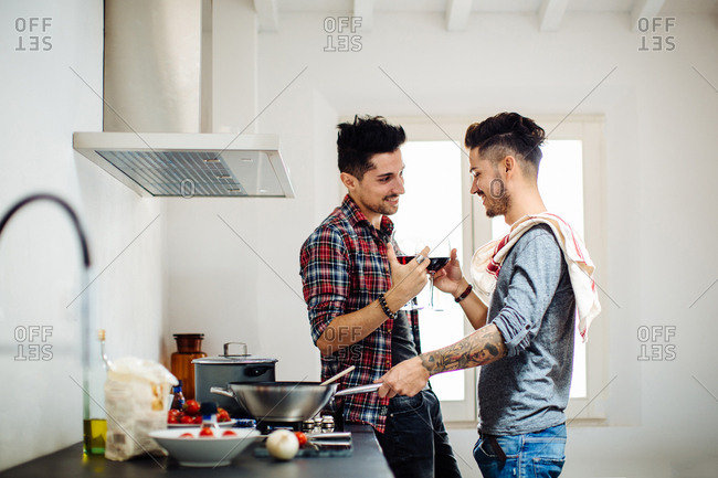 Male couple preparing meal in kitchen, drinking wine