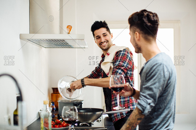 Male couple preparing meal together in kitchen, drinking wine