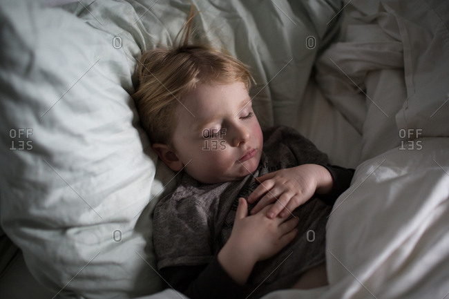 Boy sleeps in bed