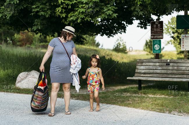 Woman carrying beach bag walks with toddler daughter