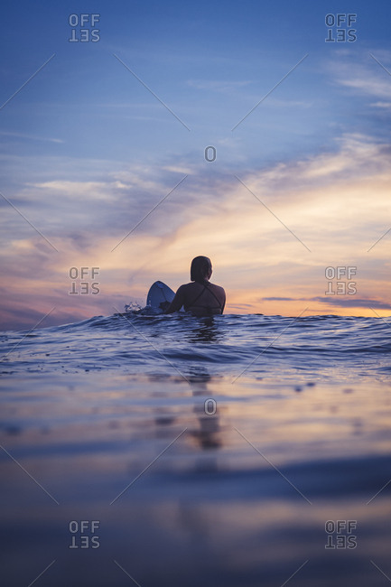 Woman waiting on her surfboard in water at dusk