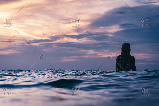 Surfer waiting for wave at sunset