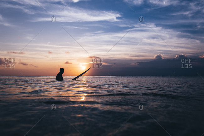 Surfer silhouetted in water at sunset