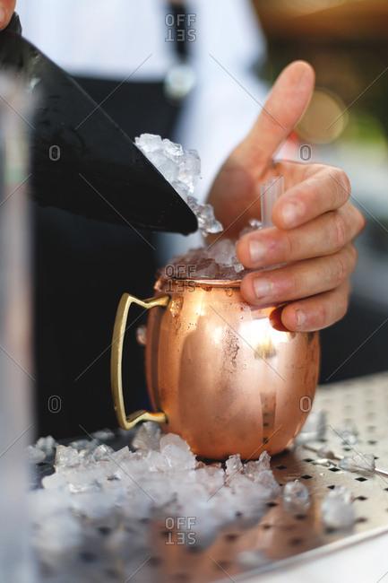 Bartender putting ice in a copper mug