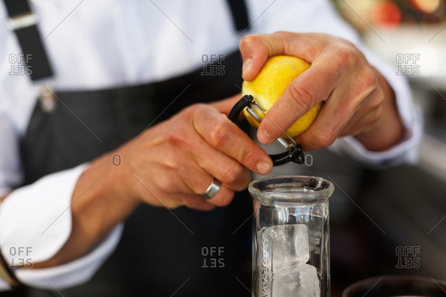 Bartender peeling strip of lemon rind for drink