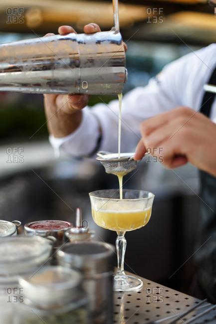 Bartender pouring drink through strainer
