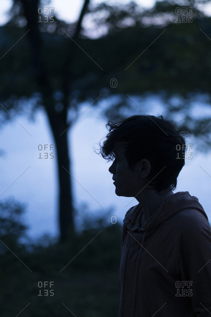 Teen boy silhouetted beside a lake