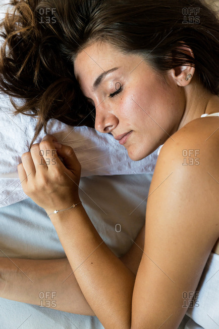 Young brunette lying in bed under blanket and sleeping in morning light