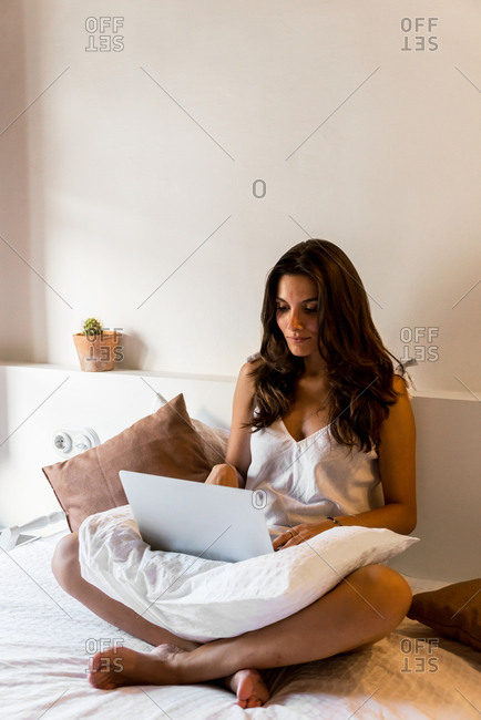 Young brunette using laptop on bed in daylight