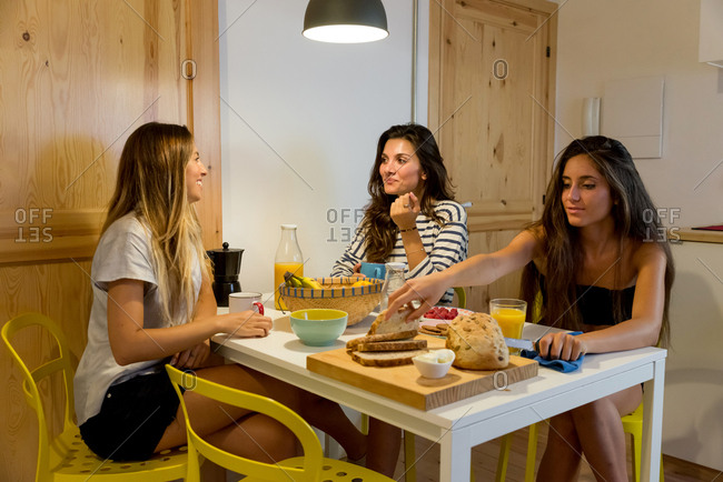 Three young girls sitting at table in modern apartment and having breakfast talking and smiling