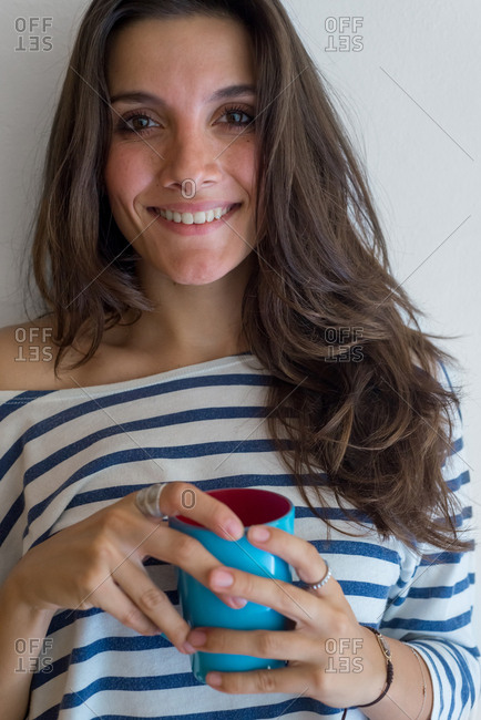 Beautiful brunette holding a mug of coffee for morning breakfast