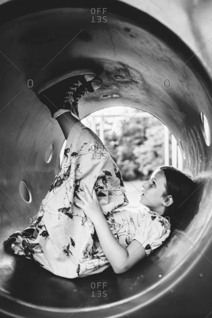 Girl in dress lying in park tunnel