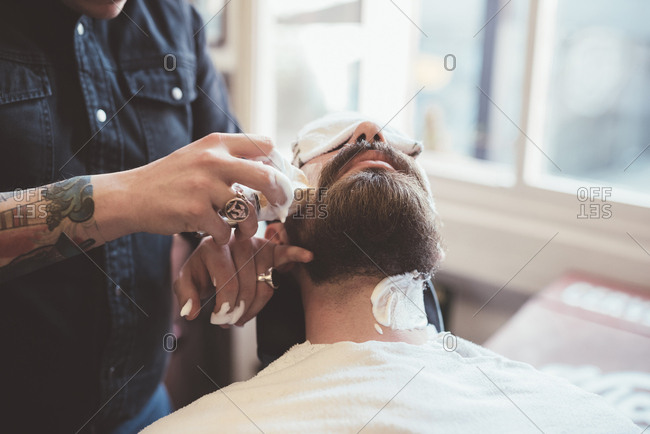 Barber applying shaving cream to clients face in barber shop
