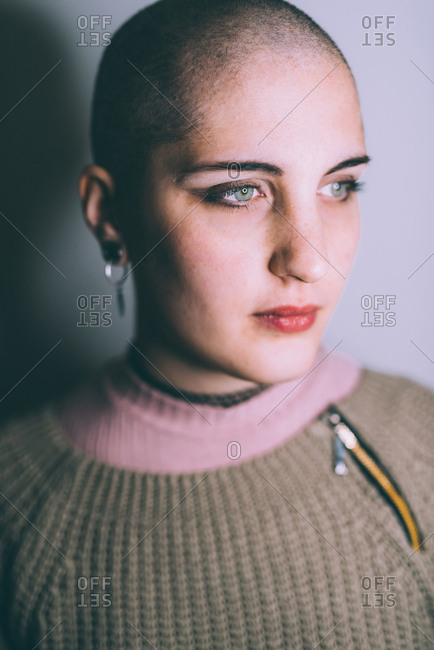 Head and shoulder portrait of blue eyed young woman with shaved head