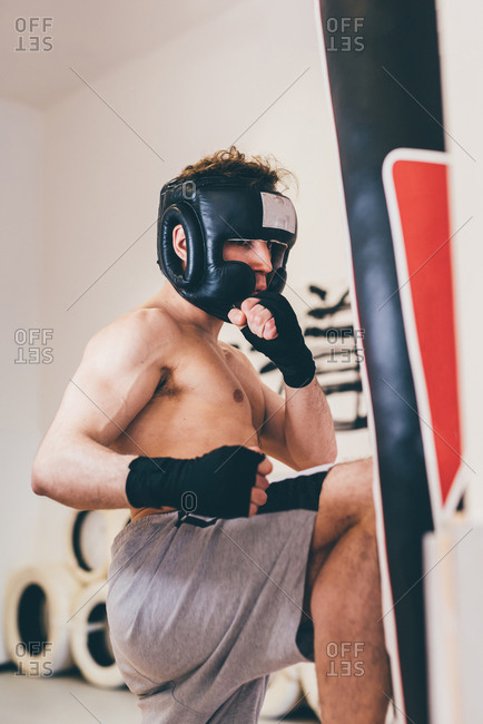 Man wearing head protector sparring with punching bag
