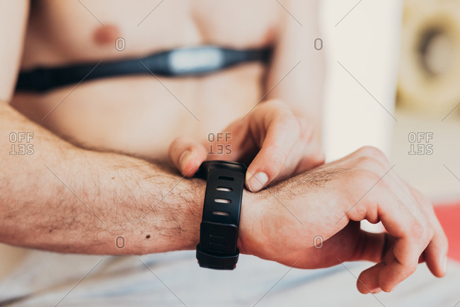 Man wearing heart rate monitor on chest checking wrist watch