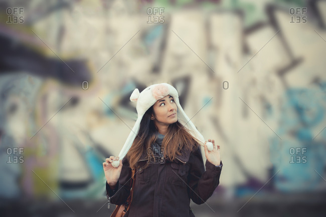 Portrait of mid adult woman wearing fur hat in front of graffiti wall