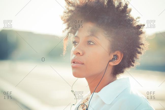 Portrait of pensive young woman listening to earphones