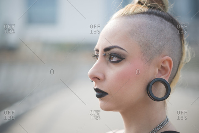 Portrait of young female punk with earlobe piercing and shaved head