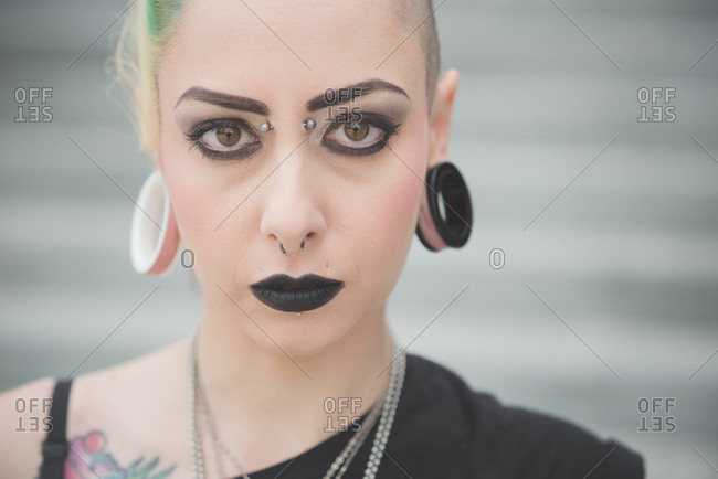 Portrait of young female punk with nose and earlobe piercings