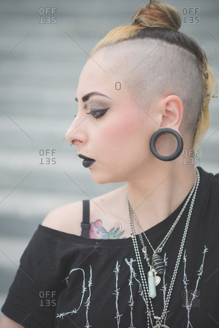 Portrait of young female punk with piercings and shaved head