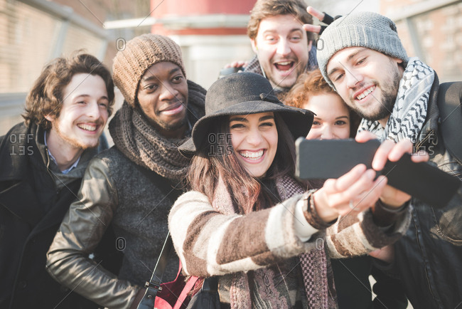 Six young adult friends taking selfie on smartphone