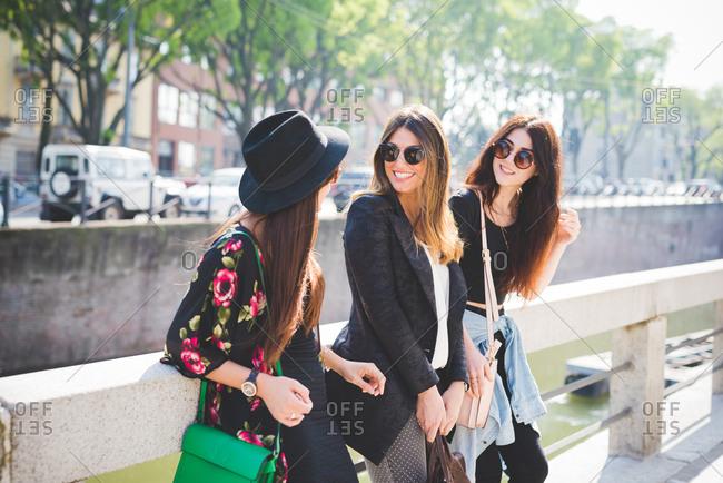 Three stylish young female friends chatting on city riverside