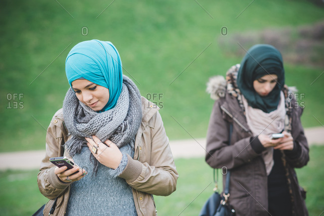 Two female friends in park reading texts on smartphones