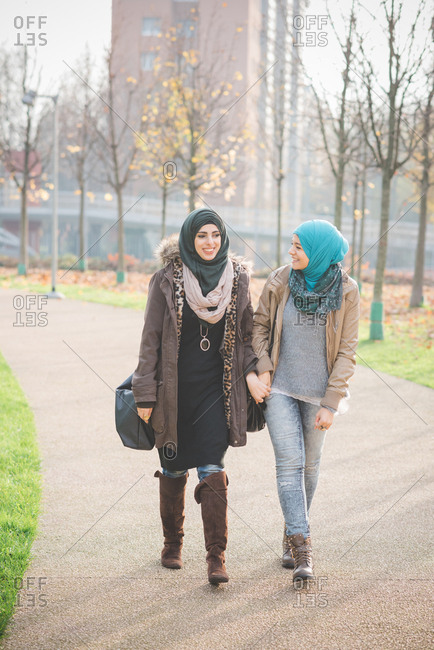 Two young women chatting whilst strolling in park