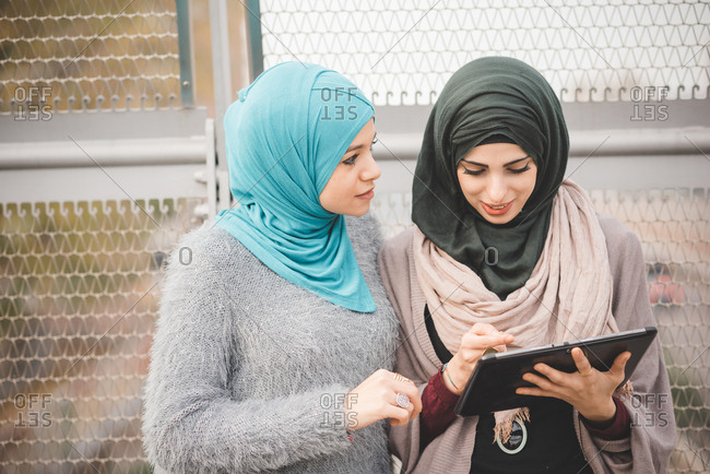 Two young women wearing hijabs using touchscreen on digital tablet on footbridge