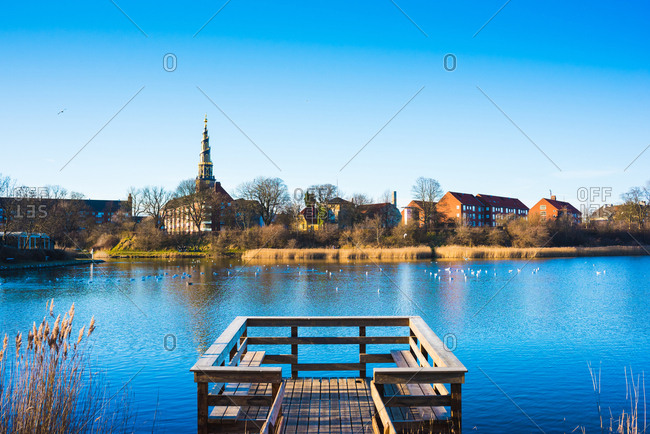 View of wooden pier on river and distant church spire, Copenhagen, Denmark