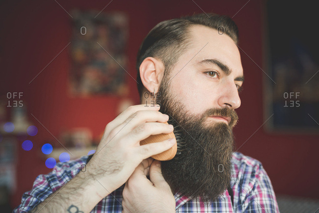 Young bearded man brushing his beard